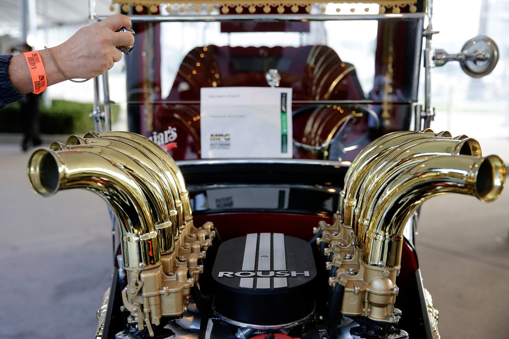 . Aja Bufka, of Czech Republic, takes pictures of the Munster\'s Koach at the 2013 Los Angeles Auto Show on Wednesday, Nov. 20, 2013, in Los Angeles. (AP Photo/Jae C. Hong)