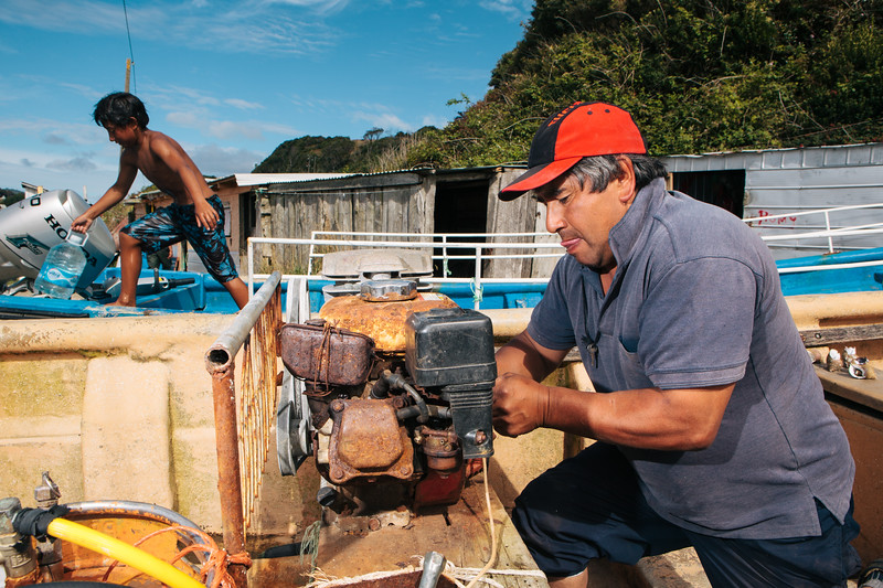 An oyster fisherman repairs his rusty dive compressor on the beach of Puñihuil. Chiloé, Chile.