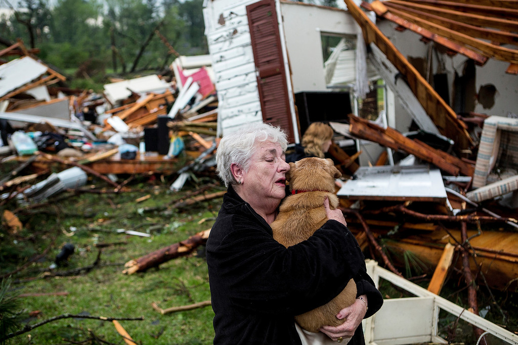 . Constance Lambert embraces her dog after finding it alive when returning to her destroyed home in Tupelo, Miss., Monday, April 28, 2014. Lambert was at an event away from her home when the tornado struck and rushed back to check on her pets. (AP Photo/The Commercial Appeal, Brad Vest)