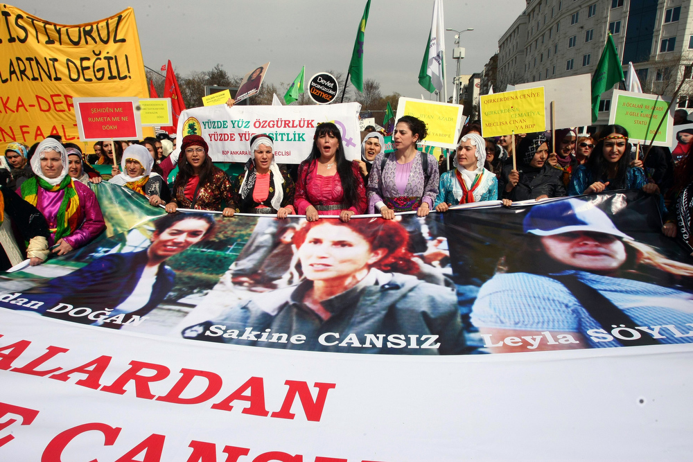 . Women march, holding a banner showing the portraits of three Kurdish activist women (from L) Fidan Dogan, Sakine Cansiz and Leyla Soylemez, found shot dead at the Kurdistan Information Bureau in Paris last January, as they commemorate the International Women\'s Day on March 8, 2013 in Ankara. Hundreds of demonstrators took part in the rally calling to stop violence towards women.   ADEM ALTAN/AFP/Getty Images