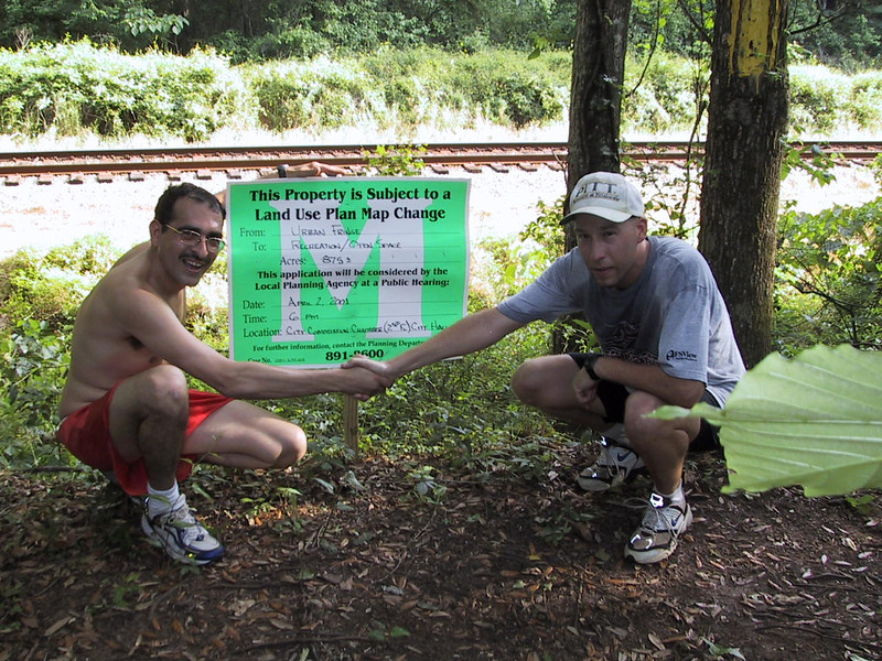 Rolando and Jeff shake celebrating this sign's proclamation that the greenway is official, even if Coupe de Ville Trail is renegade.