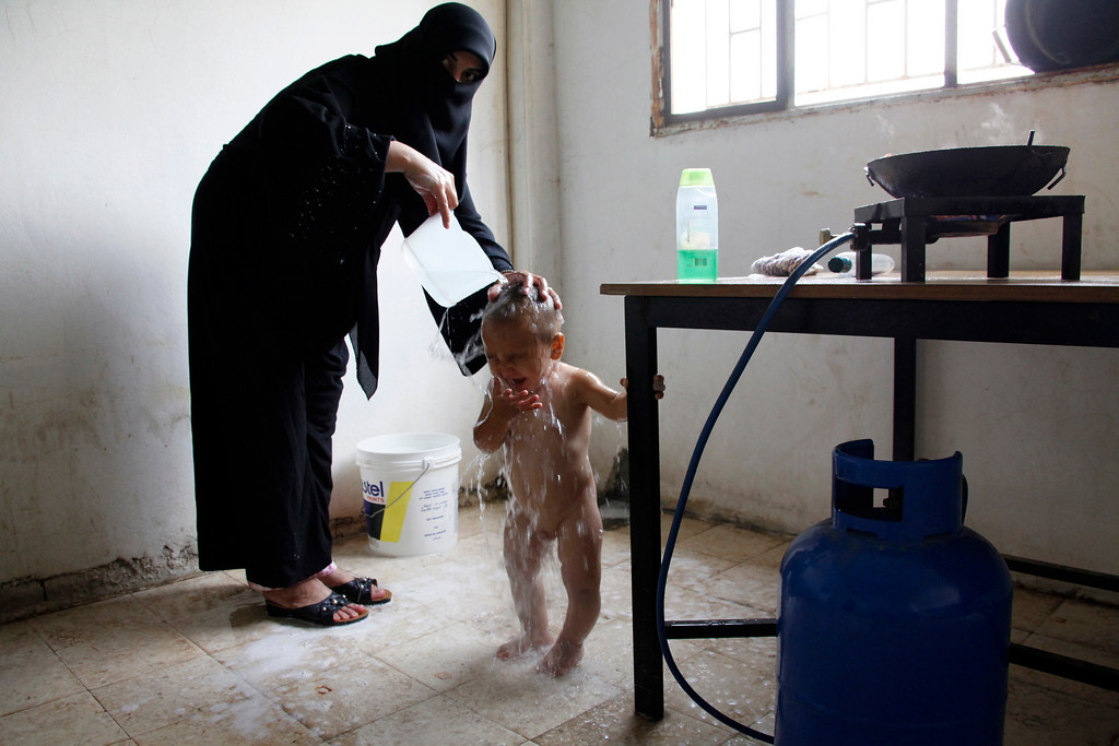 . A Syrian refugee woman gives her child a shower in the kitchen of an abandoned school in Wadi Khaled area, northern Lebanon September 28, 2011. More than 3,800 displaced Syrian refugees have registered with the United Nations refugee agency (UNHCR) in north Lebanon, which borders Syria\'s Homs province, a particularly bloody centre of the uprising against President Bashar al-Assad. REUTERS/Mohamed Azakir