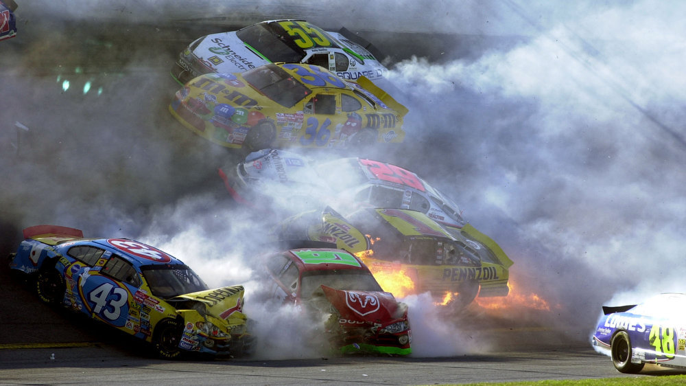Description of . Kenny Wallace's No. 1 car breaks out in flames during a 17-car crash on turn two during the 2002 Daytona 500 at Daytona International Speedway in Daytona Beach, Fla., Sunday, Feb. 17, 2002. Also involved in the crash are Bobby Hamilton (55), Ken Schrader (36), Kevin Harvick (29), John Andretti (43), Jimmie Johnson (48), and Jeremy Mayfield (19) (AP Photo/Phil Manson)