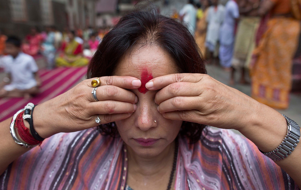 . An Indian woman performs Yoga to mark the International Yoga Day at Kamakhya temple in Gauhati, India , Wednesday, June 21, 2017. Millions of yoga enthusiasts across India take part in a mass yoga sessions to mark the third International Yoga Day which falls on June 21 every year. (AP Photo/ Anupam Nath)