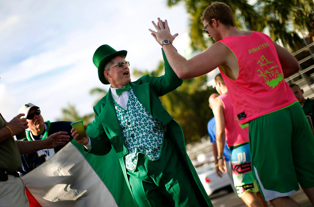 . A Notre Dame Fighting Irish fan dressed as a leprechaun high-fives another fan outside Sun Life stadium before the BCS National Championship college football game between the Alabama Crimson Tide and the Notre Dame Fighting Irish in Miami, Florida January 7, 2013. REUTERS/Mike Segar
