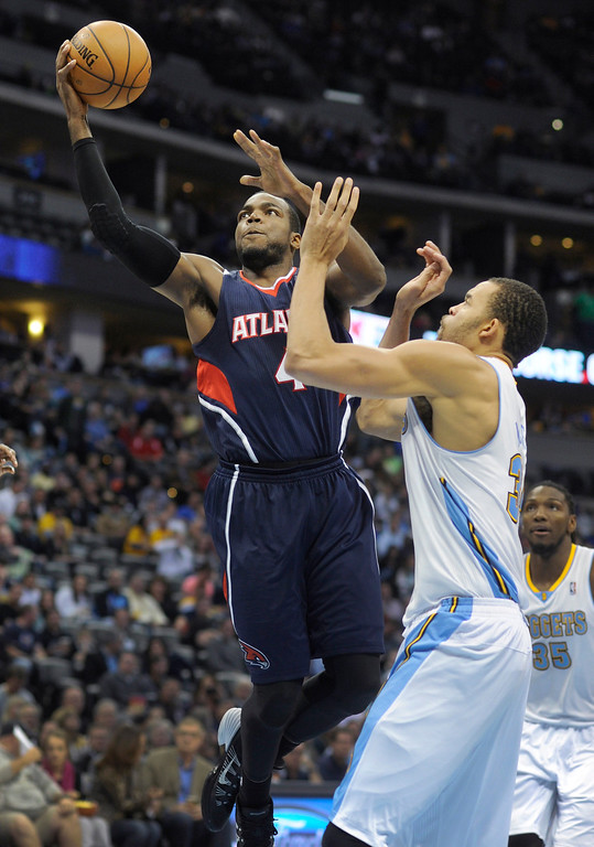 . Atlanta forward Paul Millsap (4) breezed past Denver center JaVale McGee (34) for a bucket in the second half.   Photo By Karl Gehring/The Denver Post