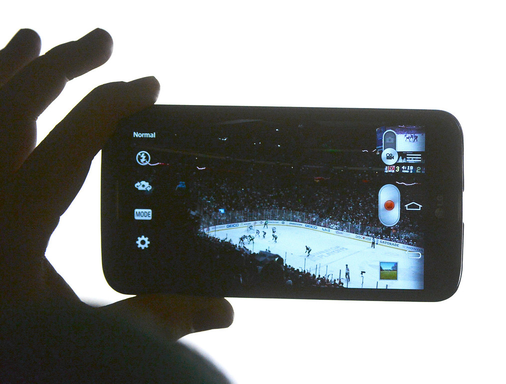 . A fan recorded the action on a cell phone late in the third period.  (Photo by Karl Gehring/The Denver Post)