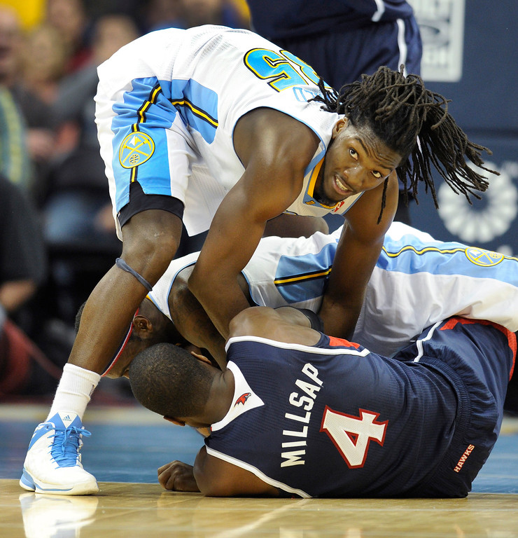 . Ty Lawson and Kenneth Faried both tried to take the ball away from Atlanta forward Paul Millsap in the fourth quarter. The Denver Nuggets defeated the Atlanta Hawks 109-107 at the Pepsi Center Thursday night, November 7, 2013 for its first win of the season.   Photo By Karl Gehring/The Denver Post