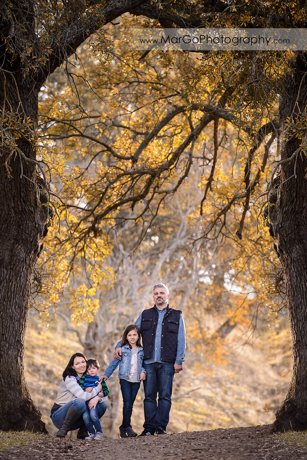 full body vertical portrait of family of four during family session at Diablo Foothills Regional Park in Walnut Creek