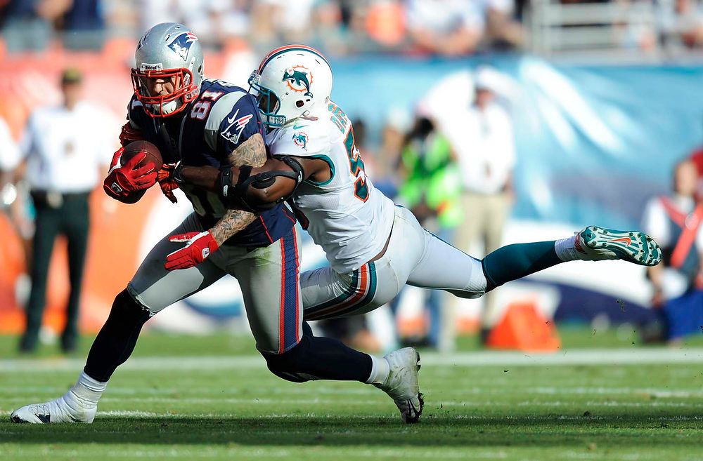 Description of . Miami Dolphins linebacker Karlos Dansby (58) grabs New England Patriots tight end Aaron Hernandez (81) during the second half of an NFL football game, Sunday, Dec. 2, 2012, in Miami. (AP Photo/Rhona Wise)