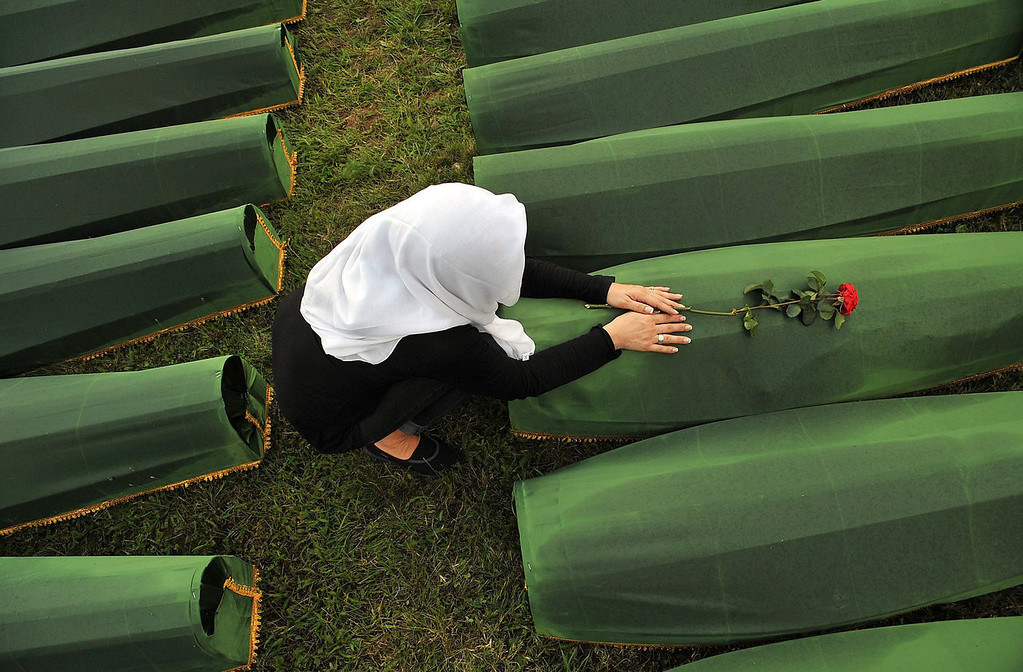 . A Bosnian Muslim woman, survivor of Srebrenica 1995 massacre, mourns over body casket of her relative, at memorial cemetery in village of Potocarion near Eastern-Bosnian town of Srebrenica, on July 10, 2013. Potocari Memorial cemetery is undergoing preparations for another mass burial on July 11, when 409 newly identified bodies will be put to final rest. Bodies are identified as those belonging to Bosnian Muslim victims, of the offensive undertaken by Bosnian Serbs in July 1995 with aim to occupy, earlier declared UN safe heaven area of Srebrenica and the surrounding villages. During the offensive more than 8000 Bosnian non-Serbs went missing to be found buried in mass graves, years after the war ended.  ELVIS BARUKCIC/AFP/Getty Images