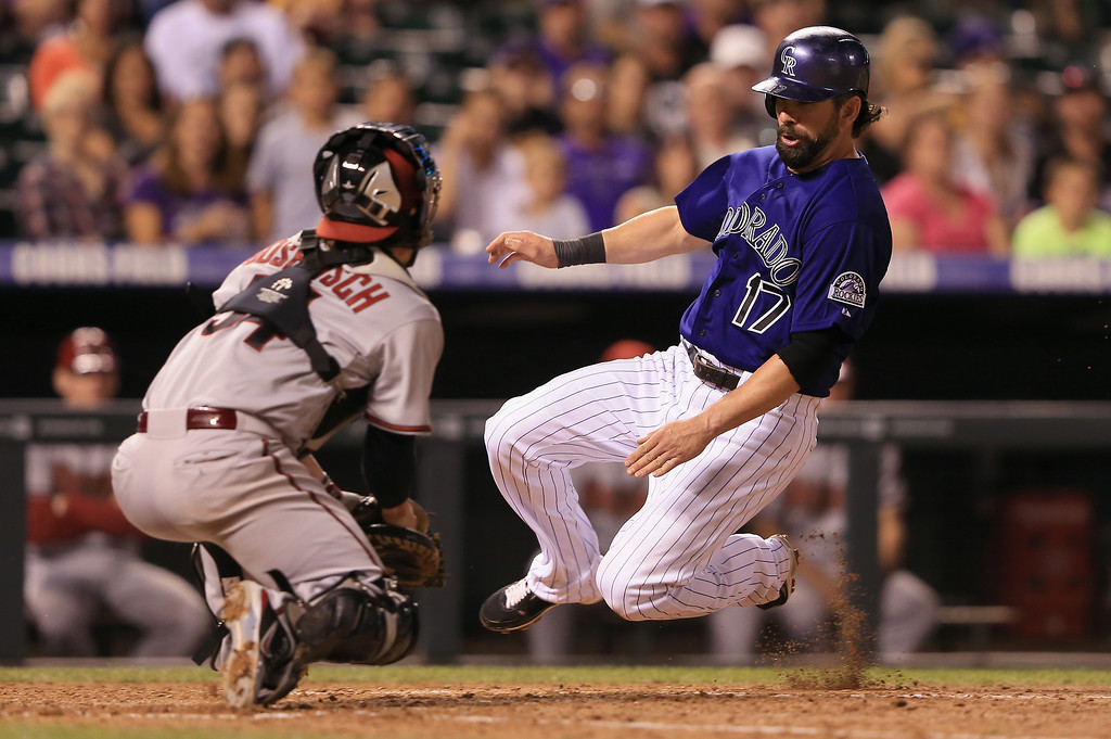 . DENVER, CO - SEPTEMBER 21:  Todd Helton #17 of the Colorado Rockies slides home past catcher Tuffy Gosewisch #54 of the Arizona Diamondbacks to score on a sacrifice fly by Jordan Pacheco #15 of the Colorado Rockies as the Diamondbacks held a 6-1 lead in the fourth inning at Coors Field on September 21, 2013 in Denver, Colorado.  (Photo by Doug Pensinger/Getty Images)