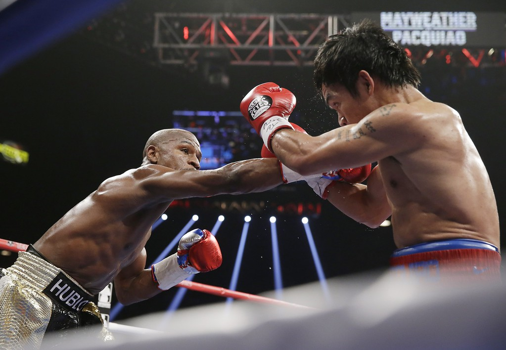 . Floyd Mayweather Jr., left, drives Manny Pacquiao, from the Philippines, back with a right to the head during their welterweight title fight on Saturday, May 2, 2015 in Las Vegas. (AP Photo/Isaac Brekken)