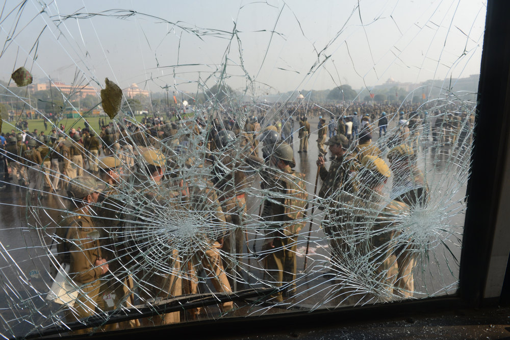 . Indian police are seen through the broken winshield of a police vehicle, inflicted by rock-throwing demonstrators, during a protest calling for  better safety for women following the rape of a student last week, in front of the Government Secretariat and Presidential Palace in New Delhi on December 22, 2012. Indian police on December 22 baton-charged, tear-gassed and fired water cannon at demonstrators who were demanding better safety for women following the brutal gang-rape of a student last weekend. Thousands of protesters, who rallied at the India Gate monument in the heart of the Indian capital and surged toward the president\'s palace, were calling for stepped-up security for women across the country. RAVEEN DRAN/AFP/Getty Images