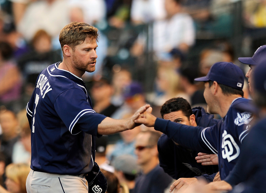 . San Diego Padres\' Chase Headley, left, is congratulated by teammates after scoring in the fourth inning of a baseball game against the Colorado Rockies, Thursday, June 6, 2013, in Denver. (AP Photo/Chris Schneider)