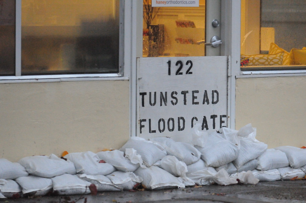 . Business owners sandbag the front of their shop in downtown San Anselmo on Thursday Dec. 11, 2014. (Robert Tong/Marin Independent Journal)