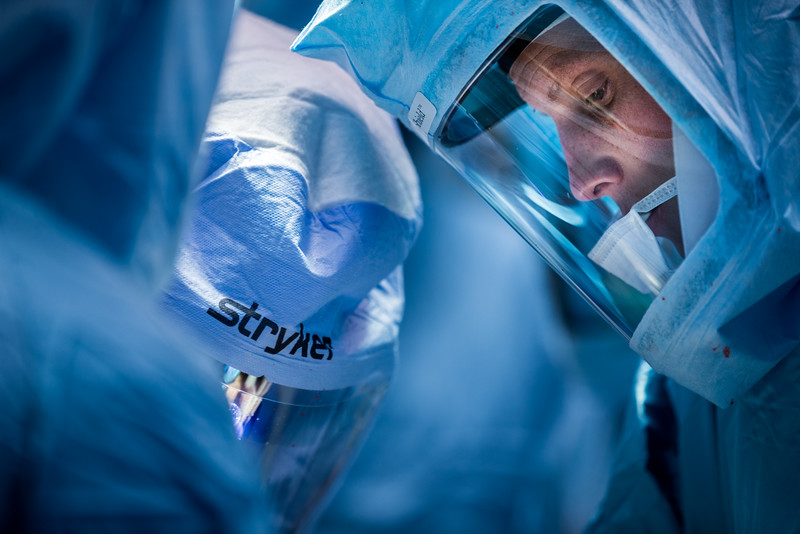 Surgeon and techs with Stryker orthopaedic Suits Concentrating During Procedure