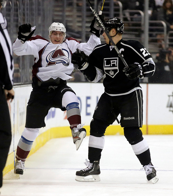 . Los Angeles Kings right wing Dustin Brown, right, checks Colorado Avalanche defenseman Tyson Barrie during the first period of an NHL hockey game, Saturday, Dec. 21, 2013, in Los Angeles. (AP Photo/Chris Carlson)