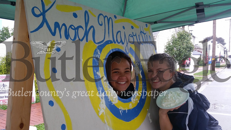 Knoch High School senior majorettes Frankie Ansell, left, and Libbey Casey demonstrate the procedure on Saturday in their booth at the rainy Saxonburg Festival of the Arts. For $2, those attending the festival could throw a pie into the face of a majorette. The fundraiser supports the majorettes.