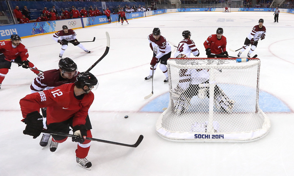 . SOCHI, RUSSIA - FEBRUARY 12: Luca Cunti #12 of Switzerland handles the puck against Arturs Kulda #32 and Edgars Masalskis #31 of Latvia in the second period during the Men\'s Ice Hockey Preliminary Round Group C game on day five of the Sochi 2014 Winter Olympics at Shayba Arena on February 12, 2014 in Sochi, Russia.  (Photo by Martin Rose/Getty Images)