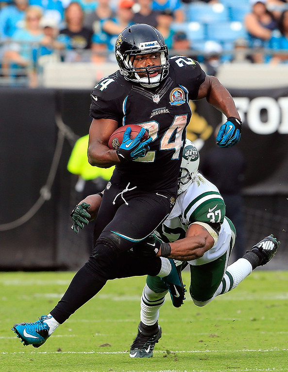 . JACKSONVILLE, FL - DECEMBER 09:   Yeremiah Bell  #37 of the New York Jets attempts to tackle Montel Owens #24 of the Jacksonville Jaguars during the game at EverBank Field on December 9, 2012 in Jacksonville, Florida.  (Photo by Sam Greenwood/Getty Images)