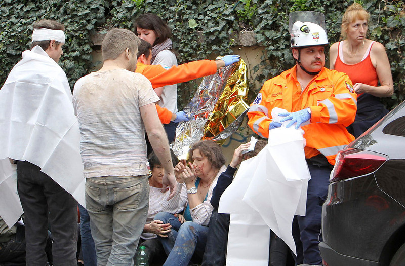 . Injured people are tended to by rescue workers after an explosion in Prague April 29, 2013. The explosion in central Prague on Monday, probably caused by gas, injured as many as 40 people, officials said, and neighboring buildings - including the National Theatre - had to be evacuated.      REUTERS/David W Cerny