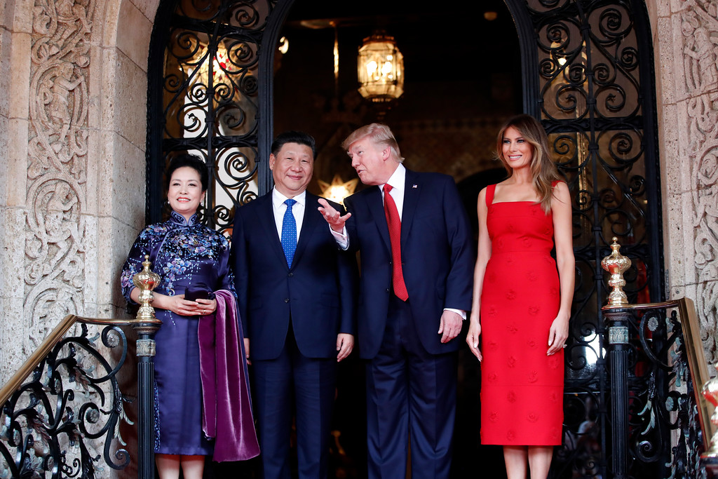 . President Donald Trump talks with Chinese President Xi Jinping, with their wives, first lady Melania Trump and Chinese first lady Peng Liyuan as they pose for photographers before dinner at Mar-a-Lago, Thursday, April 6, 2017, in Palm Beach, Fla. (AP Photo/Alex Brandon)