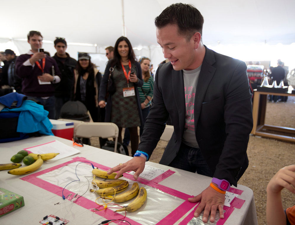 . Steven Quintanilla plays a tune on bananas inside the create tent on Red River Street in Austin, Texas, during the SXSW Interactive Festival on Monday, March 11, 2013. (AP Photo/American-Statesman, Deborah Cannon)