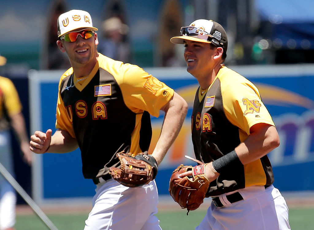 . U.S. Team\'s Ryon Healy, right, of the Oakland Athletics, and Hunter Dozier, of the Kansas City Royals, take the field prior to the All-Star Futures baseball game against the World team, Sunday, July 10, 2016, in San Diego. (AP Photo/Matt York)