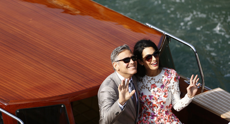 """. US actor George Clooney and his wife Amal Alamuddin stand on a taxi boat on the Grand Canal on September 28, 2014 in Venice. Hollywood heartthrob George Clooney and Lebanese-British lawyer Amal Alamuddin married in Venice on Saturday September 27, 2014 before partying the night away with their A-list friends in one of the most high-profile celebrity weddings in years. \""""George Clooney and Amal Alamuddin were married today (September 27) in a private ceremony in Venice, Italy,\"""" Clooney spokesman Stan Rosenfield said. The announcement came as a surprise as the pair were not expected to officially tie the knot until Monday, though they are still tipped for a civil ceremony at the town hall to make the marriage official under Italian law.  PIERRE TEYSSOT/AFP/Getty Images"""