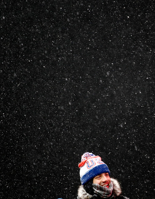 . A USA fan watches in the snow during final heats of the men\'s luge competition at the 2018 Winter Olympics in Pyeongchang, South Korea, Sunday, Feb. 11, 2018. (AP Photo/Charlie Riedel)