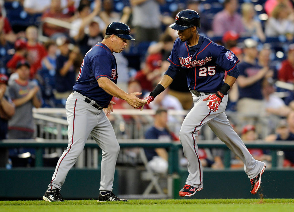 . Minnesota Twins\' Pedro Florimon (25) is greeted by third base coach Joe Vavra (46) after he hit a two-run home run against the Washington Nationals during the third inning.  (AP Photo/Nick Wass)