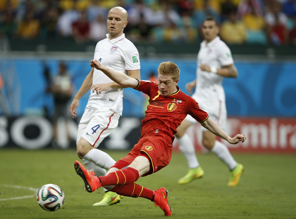 . US midfielder Michael Bradley (L) looks on as Belgium\'s midfielder Kevin De Bruyne kicks the ball during the Round of 16 football match between Belgium and USA at The Fonte Nova Arena in Salvador on July 1, 2014, during the 2014 FIFA World Cup. AFP PHOTO / ADRIAN  DENNIS/AFP/Getty Images