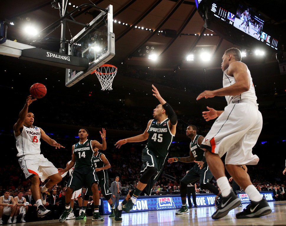 . Malcolm Brogdon #15 of the Virginia Cavaliers looks to pass the ball against Denzel Valentine #45 of the Michigan State Spartans during the regional semifinal of the 2014 NCAA Men\'s Basketball Tournament at Madison Square Garden on March 28, 2014 in New York City.  (Photo by Bruce Bennett/Getty Images)