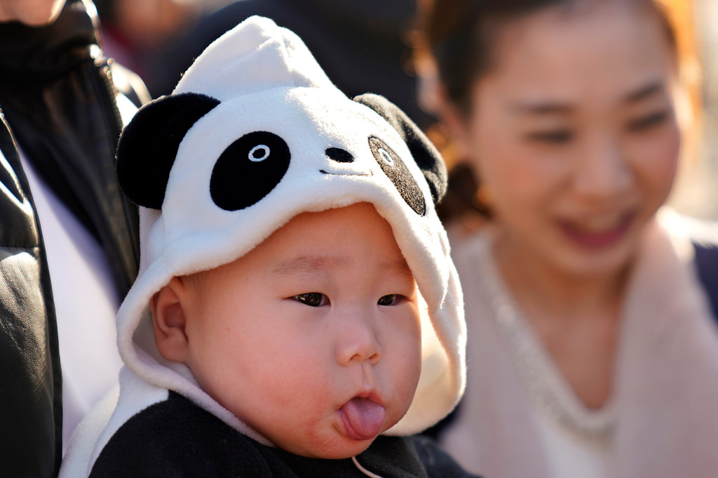 . Miu Suwazono, a 6-month-old girl, wearing clothes featuring panda waits at Ueno Zoo to see 6-month-old female giant panda cub Xiang Xiang during its public viewing in Tokyo, Tuesday, Dec. 19, 2017.  Tokyo�s new idol, baby panda Xiang Xiang, formally debuted Tuesday, immediately melting the hearts of hundreds of fans decorating themselves with panda motifs who visited the zoo and the neighborhood filled with festivity.(AP Photo/Shizuo Kambayashi)
