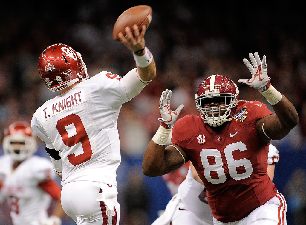 . NEW ORLEANS, LA - JANUARY 02: Trevor Knight #9 of the Oklahoma Sooners is pressured by A\'Shawn Robinson #86 of the Alabama Crimson Tide during the Allstate Sugar Bowl at the Mercedes-Benz Superdome on January 2, 2014 in New Orleans, Louisiana.  (Photo by Stacy Revere/Getty Images)