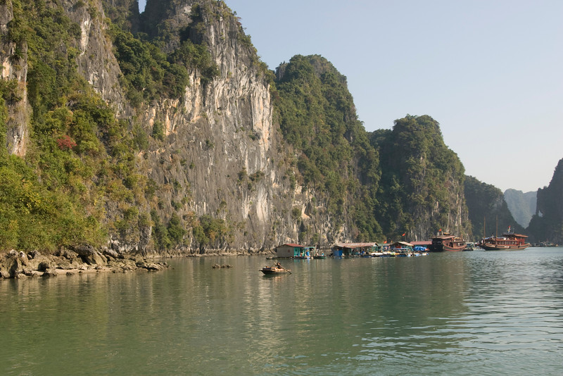 Floating houses near steep rock cliffs in Ha Long Bay, Vietnam