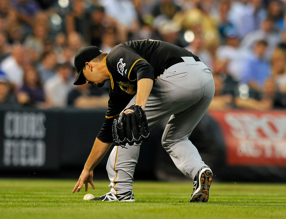 . Pittsburgh Pirates starting pitcher Charlie Morton fields a bloop single hit by Colorado Rockies Nolan Arenado in the fourth inning of a baseball game on Friday, July 25, 2014, in Denver. (AP Photo/Chris Schneider)