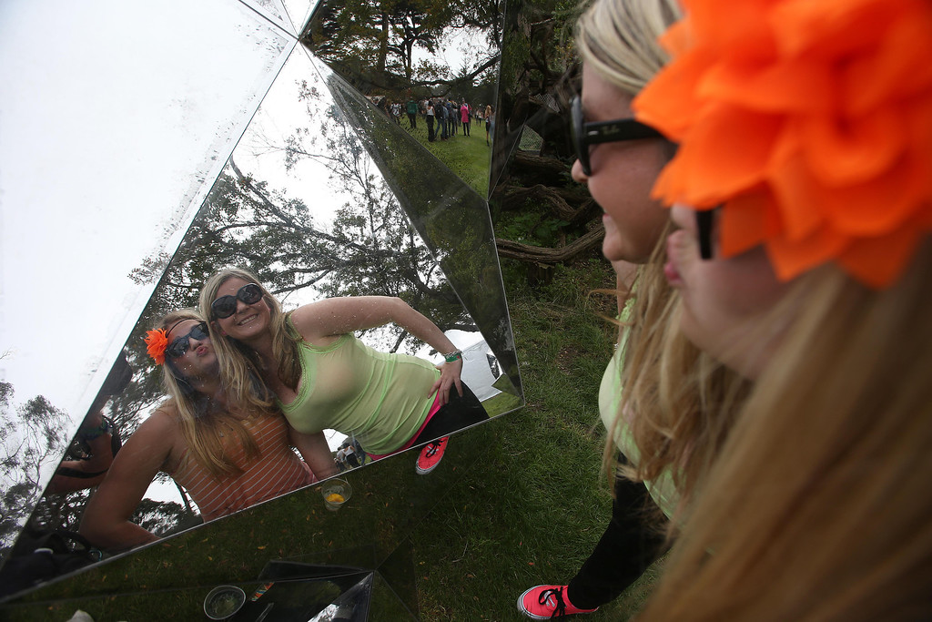 . Katy Berrey, left, and Rachel Dixon, of Santa Barbara, pose as they take pictures by a mirror sculpture during the 6th annual Outside Lands Music and Arts Festival in Golden Gate Park in San Francisco, Calif., on Friday, Aug. 9, 2013. (Jane Tyska/Bay Area News Group)
