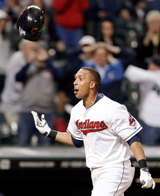 . Cleveland Indians\' Michael Brantley runs the bases and tosses his helmet before getting mobbed by teammates after hitting a solo home run off Detroit Tigers relief pitcher Al Alburquerque in the tenth inning of a baseball game Monday, May 19, 2014, in Cleveland. The Indians won 5-4 in ten innings. (AP Photo/Tony Dejak)
