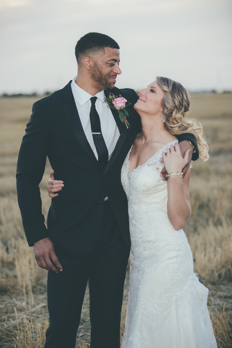 A newlywed couple smiling at one another as they look at each other standing in a field