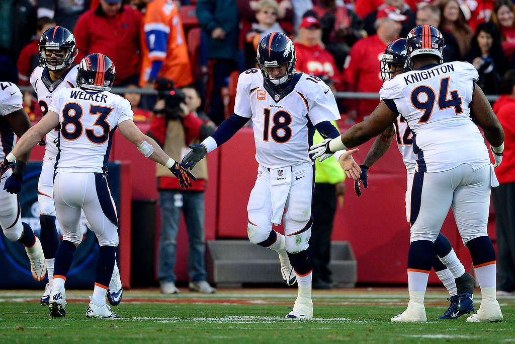 . Peyton Manning (18) of the Denver Broncos high fives teammates after throwing a touchdown to Eric Decker (87) of the Denver Broncos during the first half of the Broncos\' 35-28 win at Arrowhead Stadium.  (Photo by AAron Ontiveroz/The Denver Post)