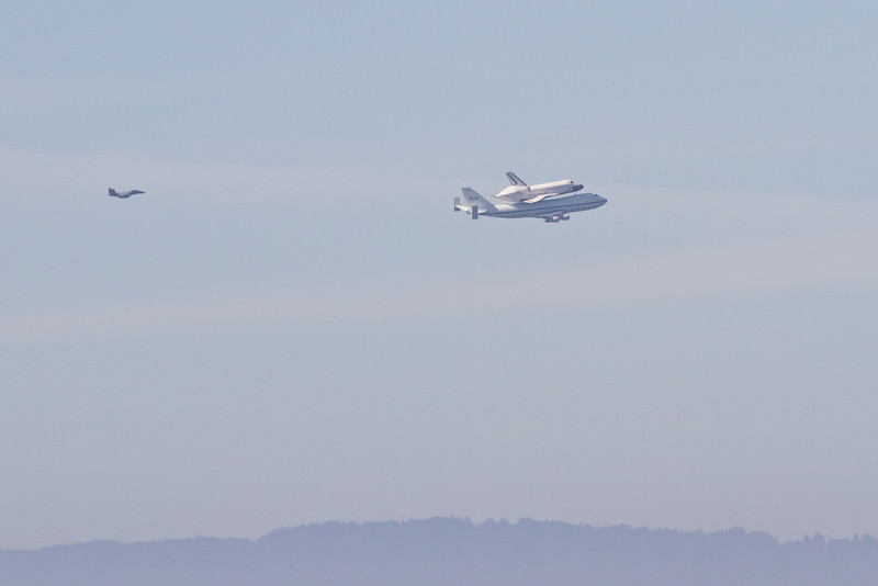 """Space shuttle """"Endeavour"""" on top the modified 747 doing a flyover of the San Francisco Bay Area. This is looking west and the hills of the peninsula are in the background. Taken from Fairmont Ridge."""
