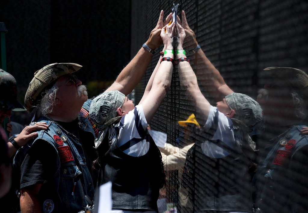 . People  make rubbings of a name on the Vietnam Veteran\'s Memorial during the Rolling Thunder ride in Washington May 26, 2013. The 26th Annual Rolling Thunder is organised to show support for veterans past and present, and those who have fallen in war or missing in action. REUTERS/Joshua Roberts