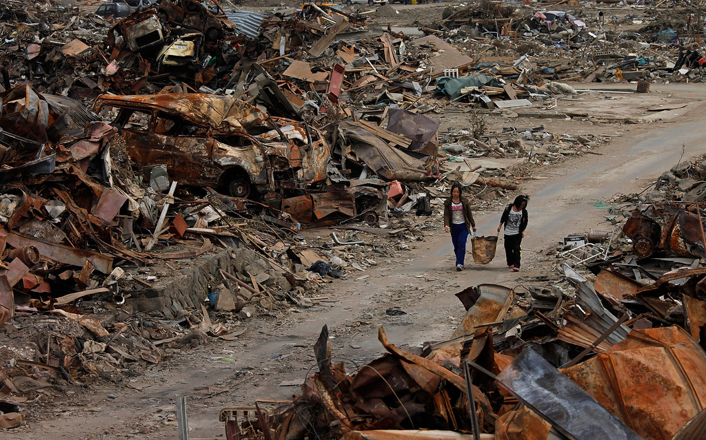 . FILE - In this Thursday, April 7, 2011, file photo, two women walk past debris in an area devastated by the March 11 earthquake and tsunami in Ishinomaki, Miyagi Prefecture, northern Japan. (AP Photo/Vincent Yu)