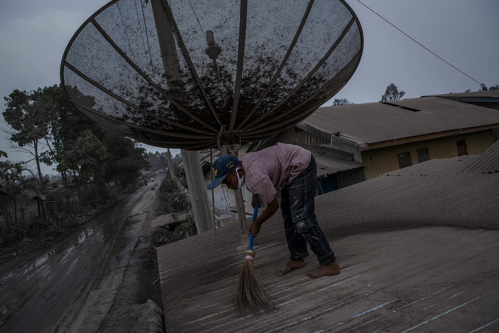 . A boy cleans his house as their village is hit by ash from the eruption of Mount Sinabung on October 13, 2014 in Berastagi, Karo district, North Sumatra, Indonesia.  (Photo by Ulet Ifansasti/Getty Images)