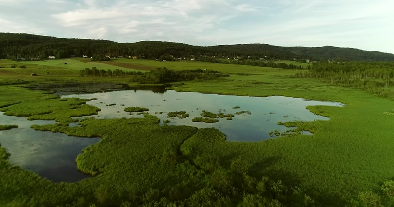 Aerial: flight over meadows towards a lake in a wide valley