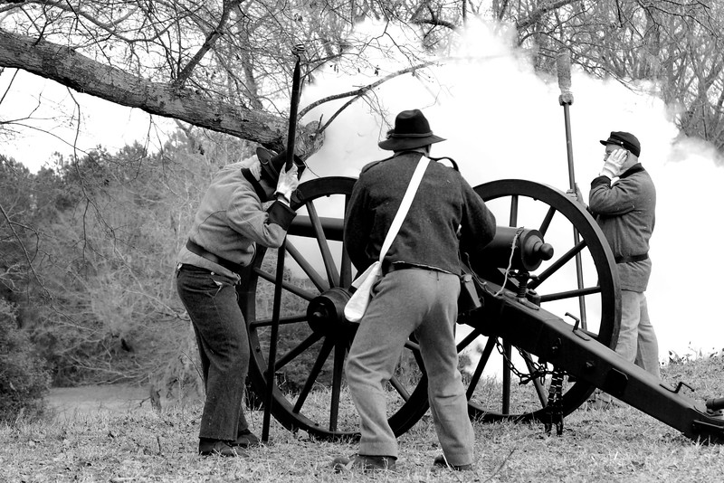 Artillery reenactors prepare to fire their canon as smoke from another canon spreads across the background. The Skirmish at Gamble's Hotel happened on March 5, 1885 when 500 federal soldiers, under the command of Reuben Williams of the 12th Indiana Infantry, marched into Florence to destroy the railroad depot but were met by Confederate soldiers backed up with 400 militia. The reenactment, held by the 23rd South Carolina Infantry, was held at the Rankin Plantation in Florence, South Carolina on Saturday, March 5, 2011. Photo Copyright 2011 Jason Barnette