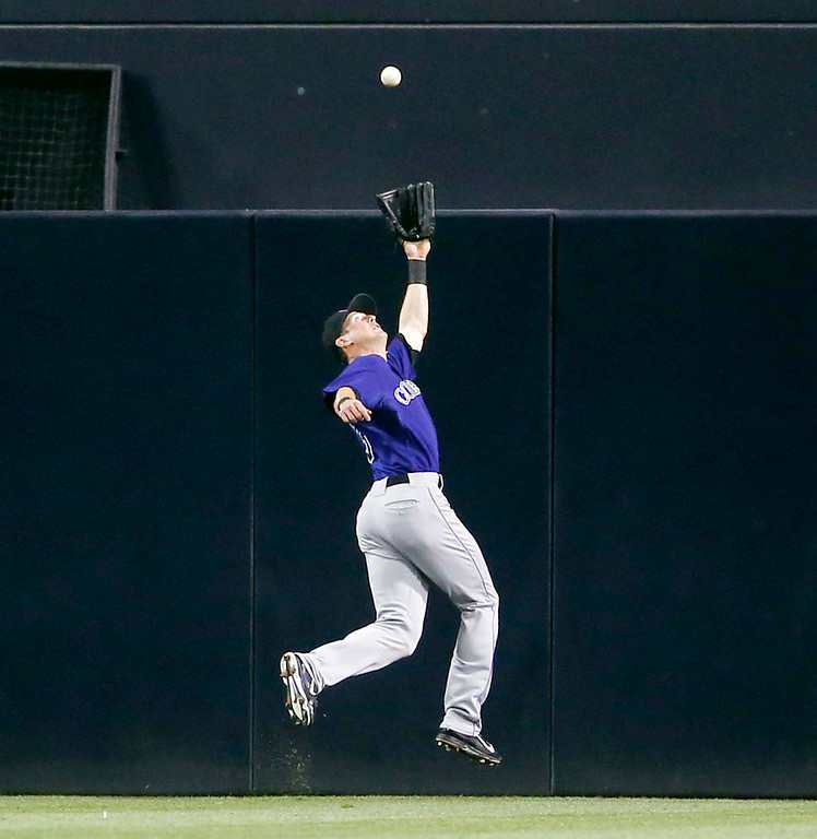 . Colorado Rockies center fielder Drew Stubbs leaps but can\'t make the catch on a double hit by San Diego Padres\' Yasmani Grandal in the fourth inning of a baseball game Monday, Aug. 11, 2014, in San Diego. The double came with Jedd Gyorkoa on first who was thrown out trying to score. (AP Photo/Lenny Ignelzi)