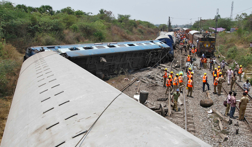 Description of . Rescue workers stand next to the derailed coaches at the site of a train accident near Arakkonam in the southern Indian state of Tamil Nadu April 10, 2013. One person was killed and dozens were injured after a passenger train derailed in Tamil Nadu, local media reported on Wednesday. REUTERS/Babu